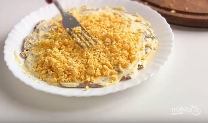 2. Яйца сварите вкрутую. Отделите желтки от белков. Натрите желток на терке и положите вторым слоем в салат.