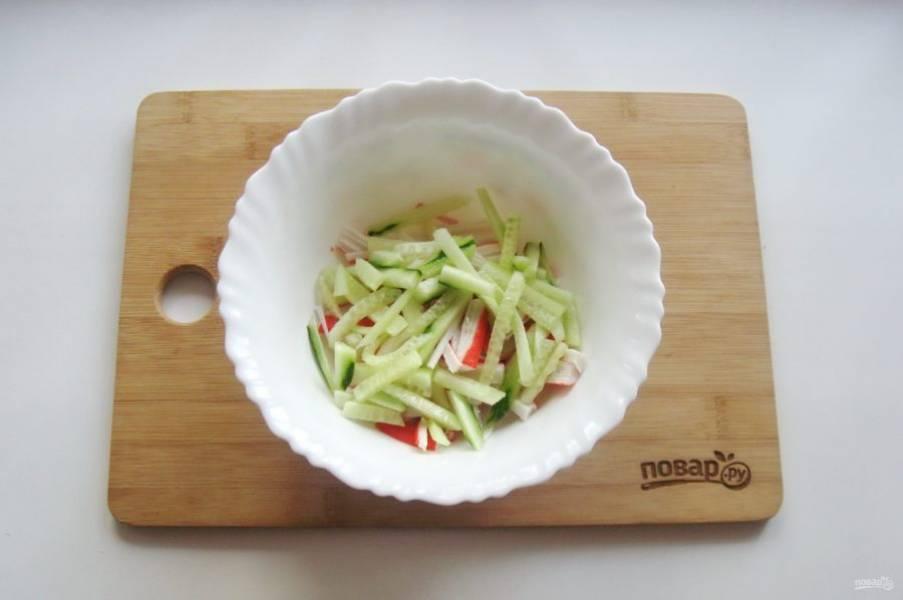 Свежий огурец также нарежьте соломкой и добавьте в салат.