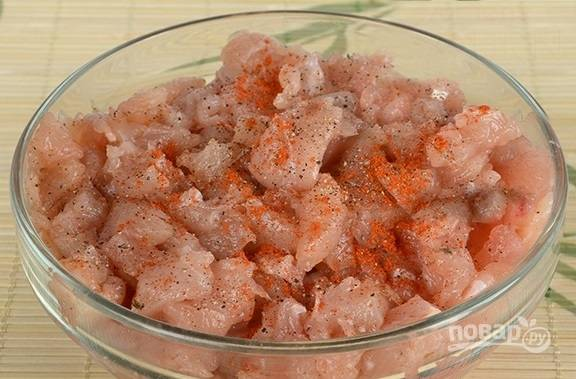 Куриное филе нарезаем маленькими кусочками, добавляем пару щепоток соли, черный молотый перец и паприку. Перемешиваем, пусть немного постоит.