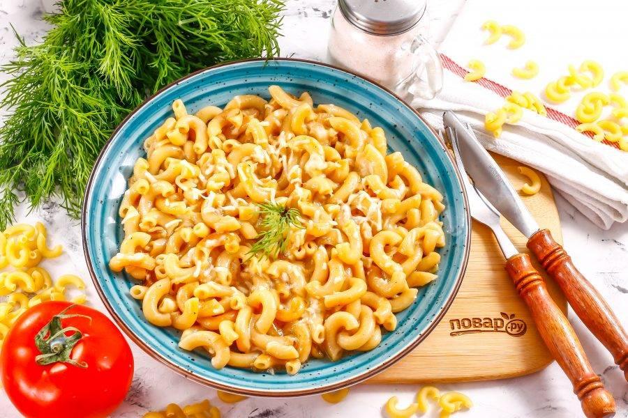 Выложите горячие макароны с расплавленным сыром на тарелки и подайте к столу.