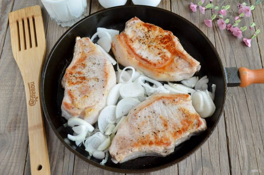 К жареному мясу добавьте лук, обжарьте его пару минут.