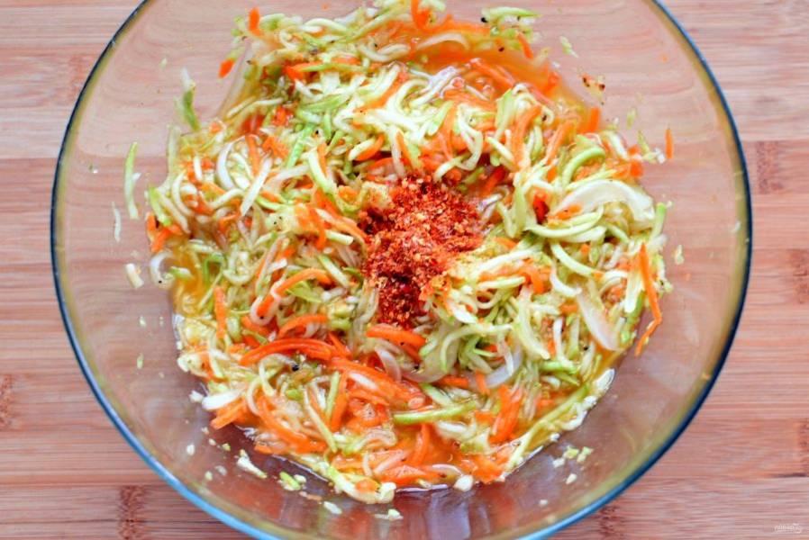 Затем соберите овощи горкой, добавьте острый перец – лучше брать хлопьями, он ароматнее – и  вылейте  сверху прогретое до дымка теплое масло. Перемешайте овощи как следует и дайте промариноваться около часа.