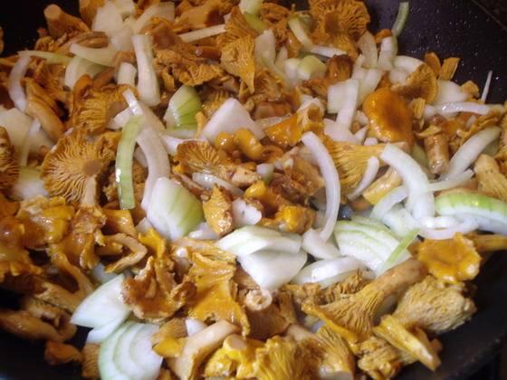 1. Растительное масло раскаляем в сковороде с перцем чили. Так, перец не будет перебивать вкус блюда. Всыпаем помытые лисички и лук. Обжарим, пока не уйдет влага от грибов.
