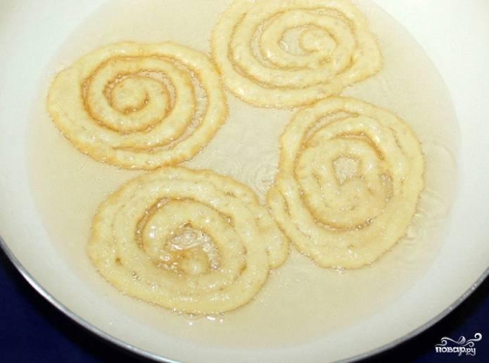 4.Принесите тесто, приступите непосредственно к приготовлению индийской сладости. Налейте в сковороду растительное масло. Наливайте его из расчета, что спирали при приготовлении будут плавать. Рисовать спирали по сковороде лучше кондитерским мешком. Допускается использовать полиэтиленовый пакет, у которого удален один из углов.