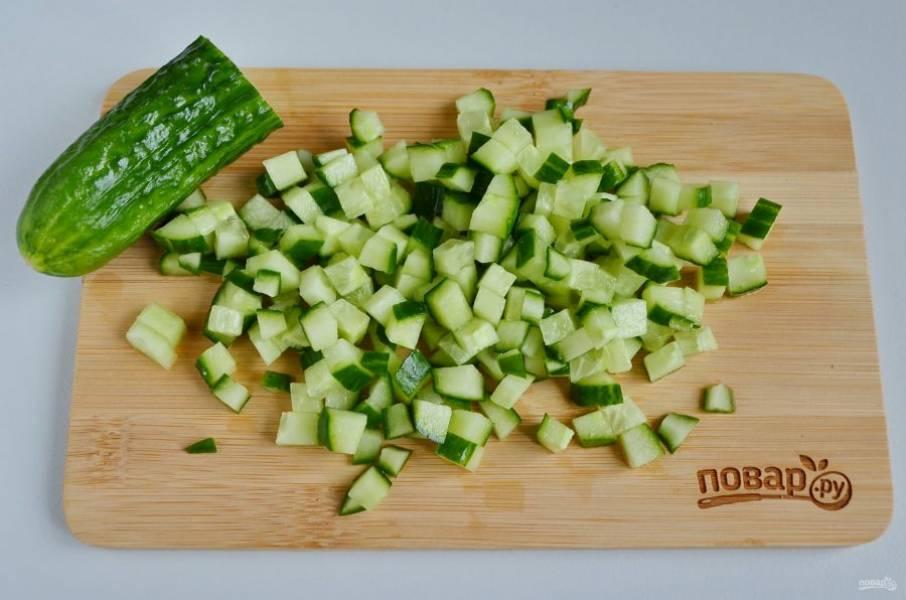 Огурчик порежьте кубиками, кусочек оставьте для украшения салата.