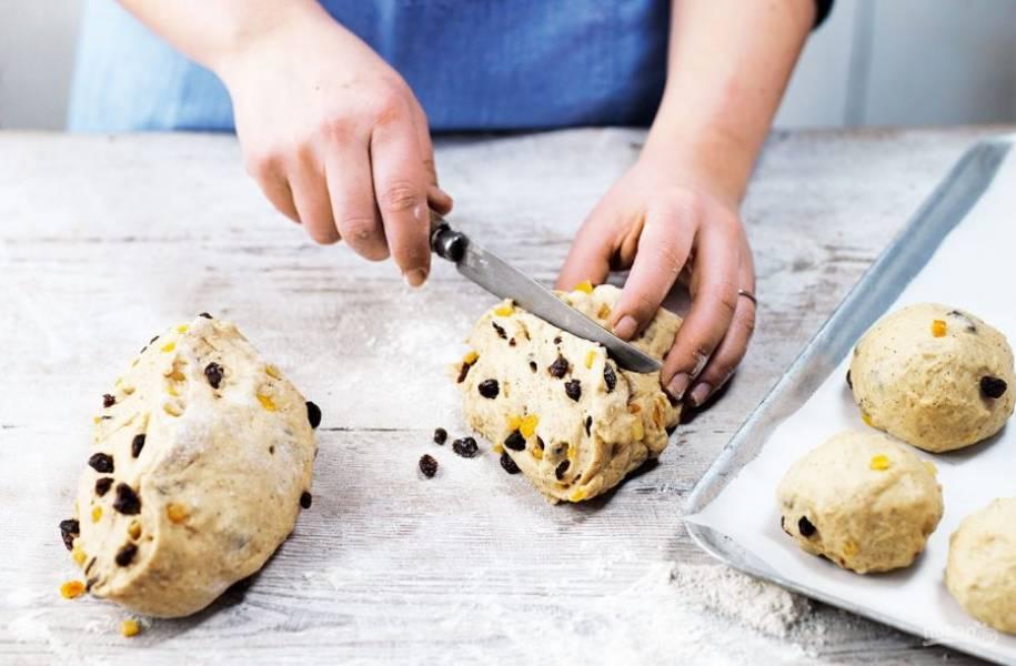 3. В пухлое тесто введите изюм, снова тщательно и равномерно замесите. Нарежьте тесто на 12 кусочков. Сформируйте круглые булочки и поместите их на противень для выпекания.