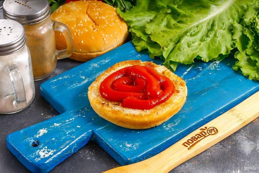 Выложите на нижнюю часть булочки соус и размажьте его.