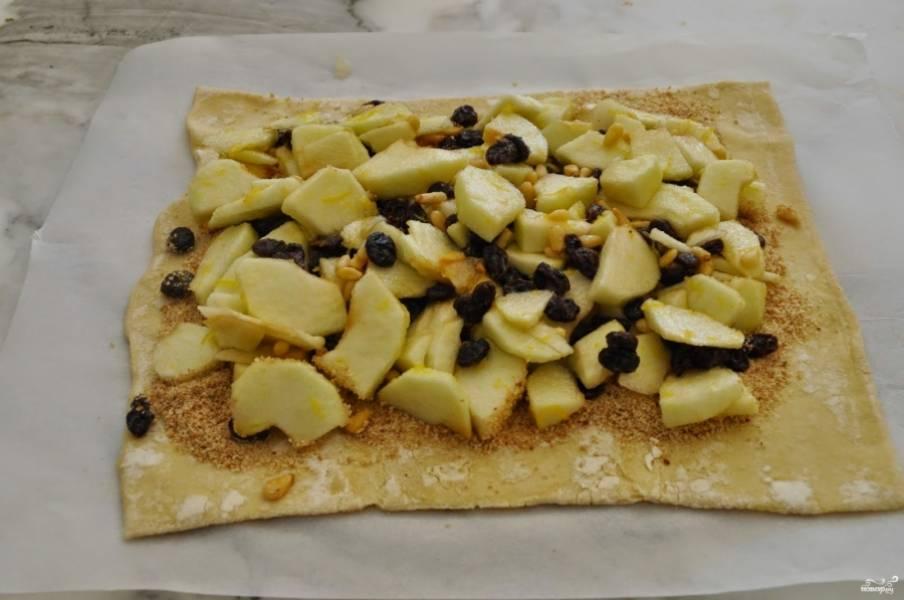 На пергаментной бумаге раскатайте слоеное тесто. Щедро сдобрите его панировочными сухарями, распределите сверху яблочную смесь.