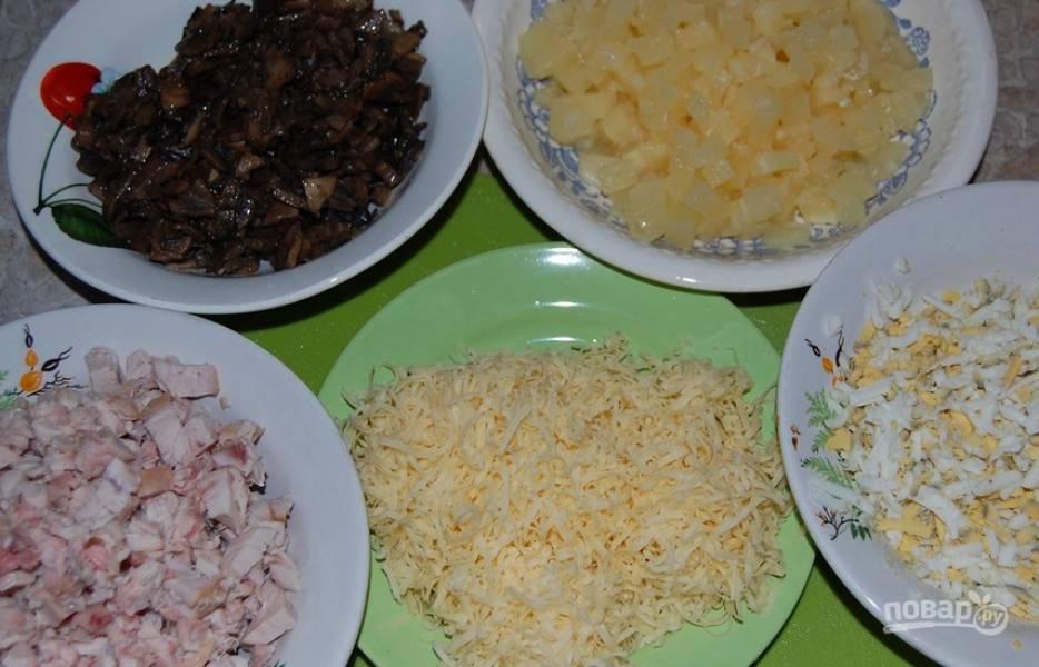 Копченую куриную грудку нарезаем кубиками. Таким же образом нарезаем ананасы. Яйца очищаем и трем на терке. Так же натрите сыр.