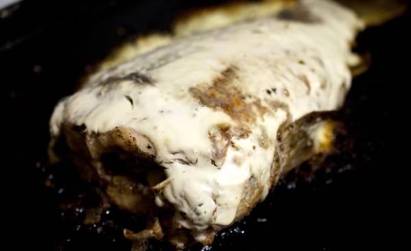 6. После этого достаньте противень, сверху (на рыбу) выложите сметану. При желании можно использовать майонез, можно даже присыпать щепоткой сыра, например. Снова отправьте противень в духовку, запекайте до готовности.