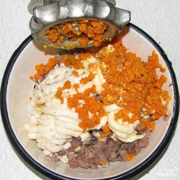 2.Сырую морковь почистите и нарежьте кусочками. С помощью мясорубки измельчите сначала кусочки селедки, затем плавленый сыр, масло, морковь.