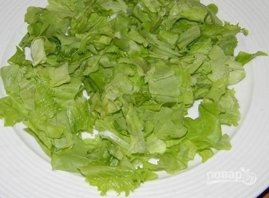Салатные листья помоем и обсушим, а затем порвем руками на кусочки и выложим на тарелку.