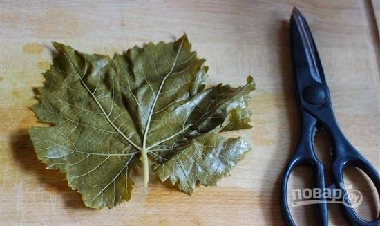 4. Жаропрочную форму застелите полностью листьями. Затем у каждого листочка отрежьте хвостик.