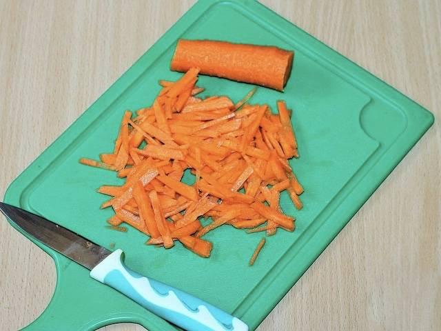 2. Теперь возьмите лук. Очистите его от шелухи, сполосните под водой и нарежьте небольшими кубиками. Морковь помойте, очистите от верхнего слоя кожуры и нарежьте соломкой (или брусочками).