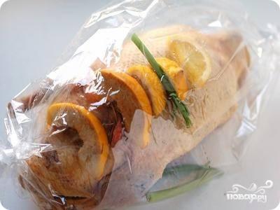 Упаковываем утку в рукав. И снова кладём на неё лимон, яблоко и орегано, посыпаем перцем и тимьяном.