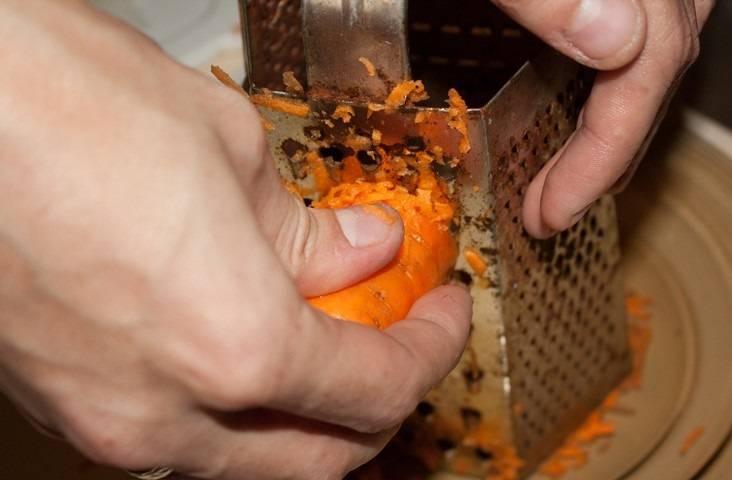 6. На терке натрите морковь, добавьте её к луку. Также по рецепту приготовления пирога с капустой и рыбной консервой можно использовать томатную пасту или соус.