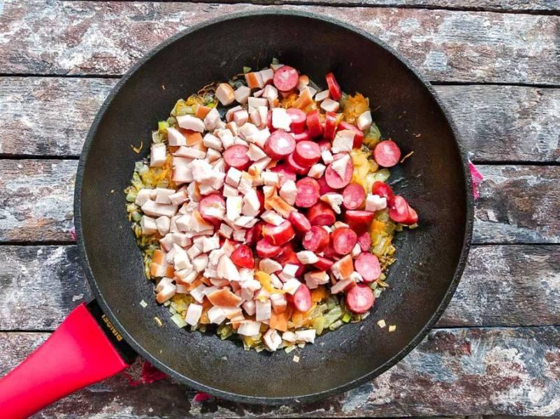 К моркови с луком добавьте колбаски, куриную грудку, все хорошо перемешайте и обжарьте в течение 4-5 минут.