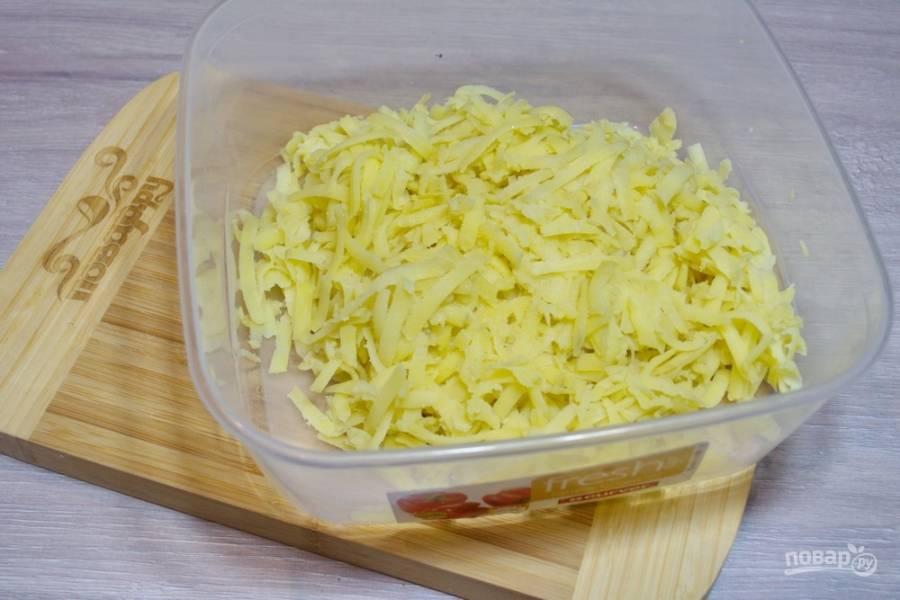 Картофель, отваренный в мундире, очистите от шкурки и натрите на крупной терке.