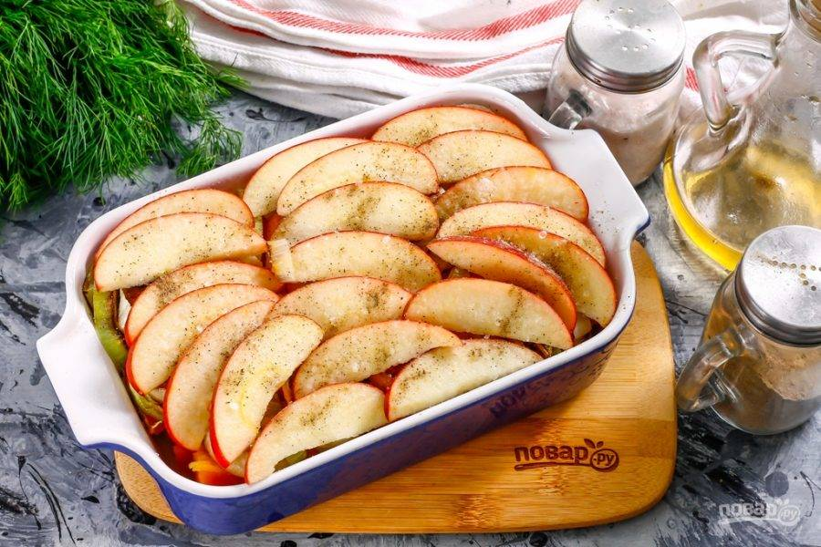 5. Разрежьте яблоко любого сорта на четыре части, вырежьте из четвертинок семенные блоки и промойте их. Нарежьте ломтиками и разложите яблочную нарезку на слое лука. Посолите ее и поперчите.
