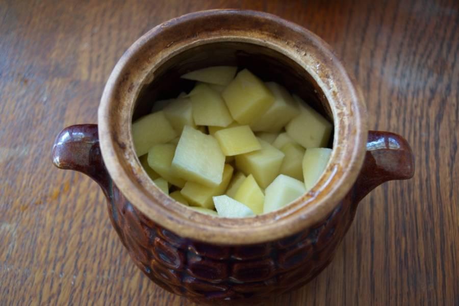 К мясу в горшочки добавляем нарезанную картошку.
