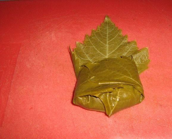 6. С виноградного листа срежьте жесткую часть, которая крепится к черешку. На середину листа выложите фарш и заверните, чтоб получился конвертик, закрытый со всех сторон.