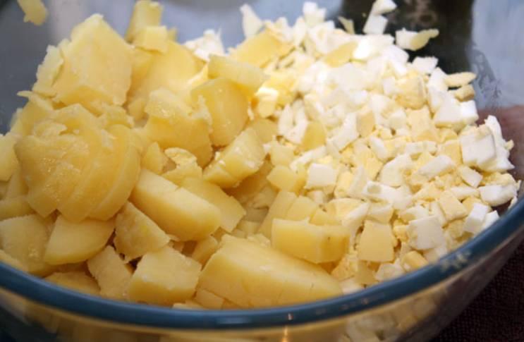 Нарезаем мелкими кубиками отварной картофель и морковь. Яйца сварим вкрутую и измельчим. Смешиваем ингредиенты.