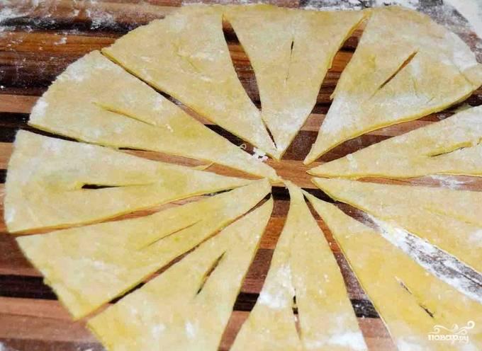 Тесто раскатываем в круг и разделяем на 6 треугольничков. Внутри каждого делаем небольшой надрез.
