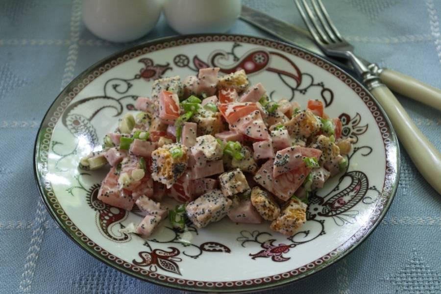 Подайте к столу салат, заправив сметаной. Любители майонеза могут добавить его вместо сметаны. Салат лучше готовить и сразу подавать к столу. От продолжительного выстаивания помидоры пустят сок, майонез и сок томатов размочат сухарики. Такой салат не годится для приготовления впрок.