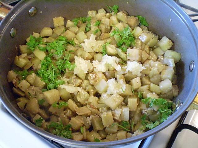 6. К готовым баклажанам добавляем чеснок и зелень.