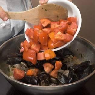 Добавьте порезанные кубиками помидоры, добавьте соль и перец чили и томите в течение 30 минут. Обжарьте хлеб и натрите свежим чесноком. Подавайте к столу горячим.