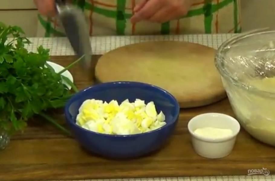 3. Приготовьте начинку: яйца отварите и нарежьте мелкими кубиками, а лук, петрушку и укроп измельчите. Посолите и поперчите по вкусу, добавьте сметану и перемешайте.