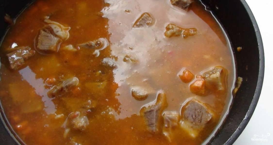 Затем в сковороду влейте бульон. Тушите подливу на слабом огне 15 минут под крышкой.
