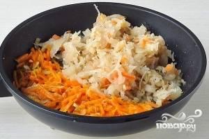 Капусту отжать и добавить в сковороду с луком и морковью. Обжаривать до тех пор, пока капуста не начнет прихватываться. После этого добавить немного воды и рассола и тушить под крышкой несколько минут.