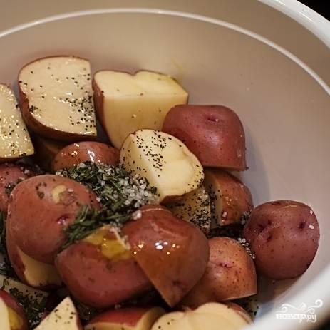 3. В большой миске (можно - закрывающейся) нарезанную картошку смешайте с солью, черным перцем (лучше крупного помола), розмарином. Залейте оливковым маслом. Закройте крышкой миску и потрясите. Можно просто смешать руками. Наша задача в том, чтобы картошка покрылась маслом и специями.