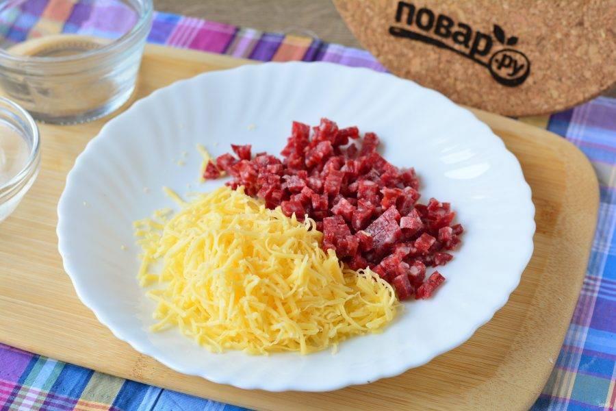 Нарежьте мелкими кубиками копченую колбасу, а сыр натрите на терке.