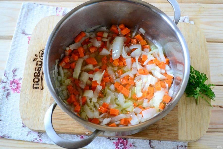 В кастрюльке, в которой будете варить супчик, разогрейте растительное масло, отправьте туда порезанный мелко лук и жарьте до мягкости. Затем добавьте натертую на крупной терке морковь и измельченный чеснок, готовьте несколько минут.