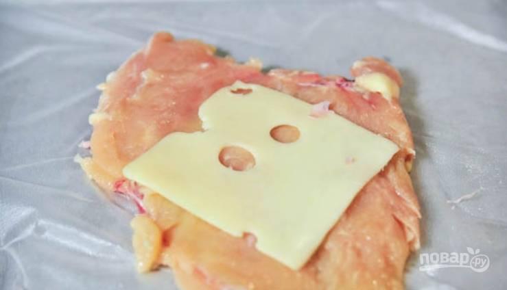 Посолите грудку и выложите на нее 1-2 пластинки сыра.