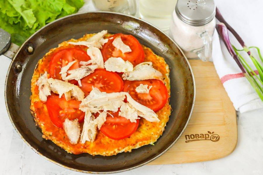 Выложите нарезку помидоров и куриное мясо.