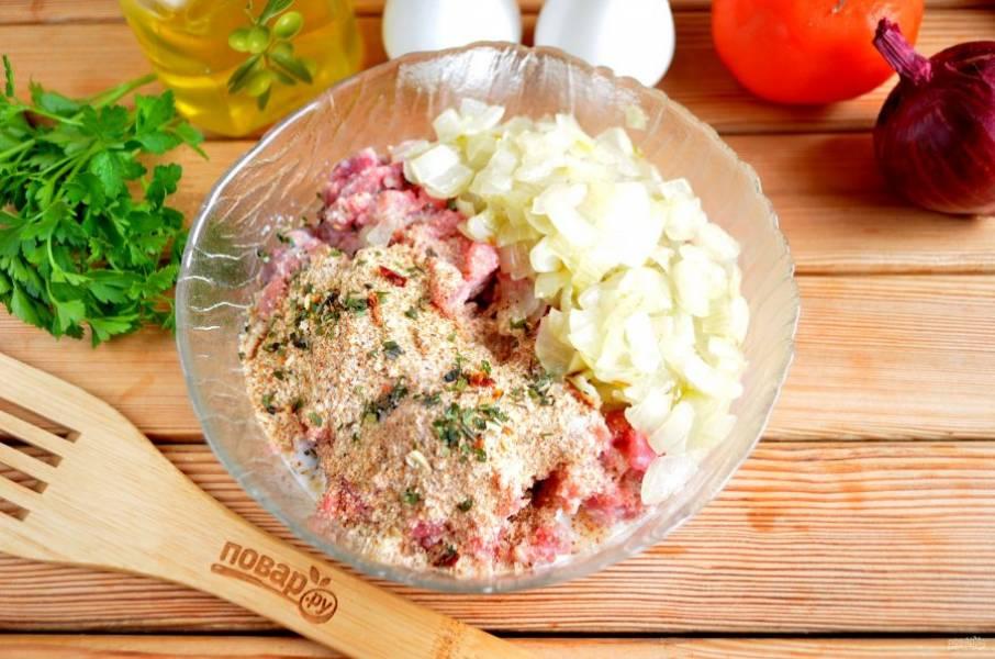 В фарш добавьте жареный лук, панировочные сухари, молоко, соль, специи.