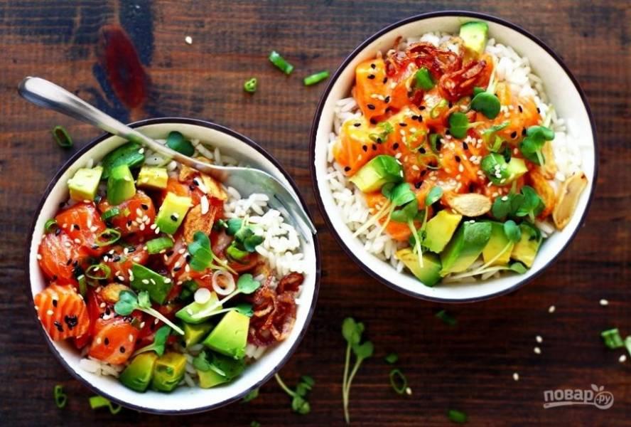 А сейчас соберите блюдо. В 3-4 чашки разложите рис. Затем рыбу, авокадо, лук и чеснок. Сверху кресс-салат и кунжут. Приятного аппетита!