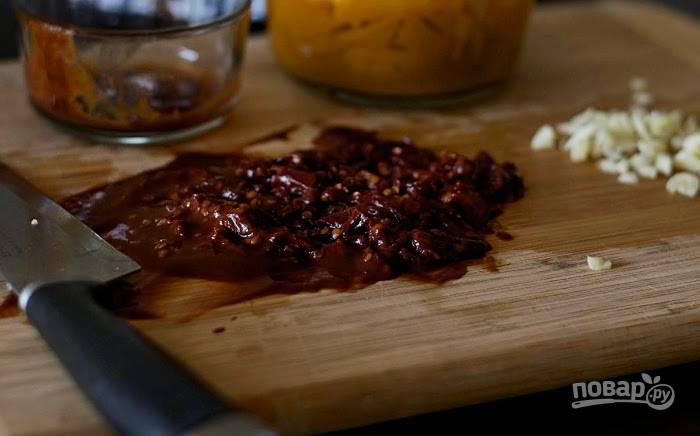 2. Затем мелко нарежьте чеснок и перец. Добавьте их в кастрюлю. Помешивая, готовьте ещё 1 минуту.