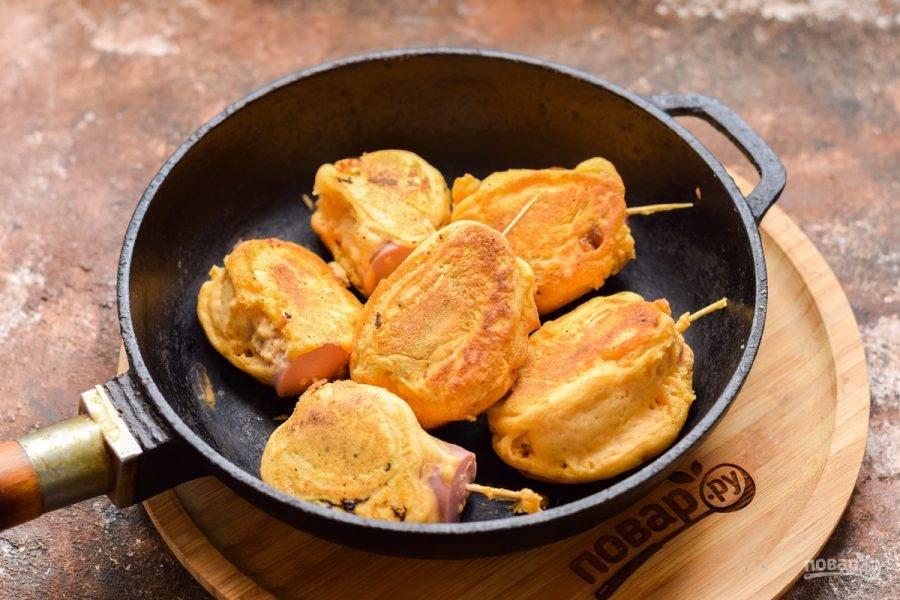 Сковороду разогрейте и влейте растительное масло. После выложите в сковороду заготовки сосисок, жарьте на среднем огне по 1,5 минуты с каждой стороны.