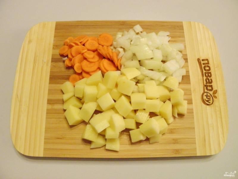 Порежьте некрупно лук, морковь и картофель. Их первыми закладывайте в кипящую воду, варите 15 минут.