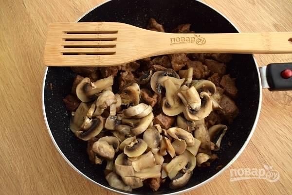 Добавьте черный свежемолотый перец, грибы, перемешайте и готовьте пару минут.