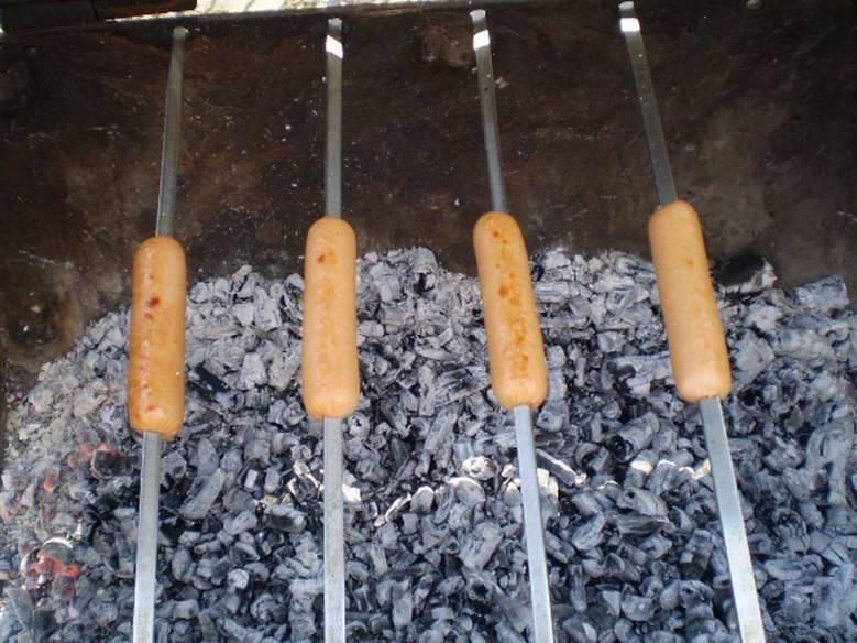 5. Переворачивайте шампура активно, чтобы сосиски не пригорели. Жарьте до румяности.