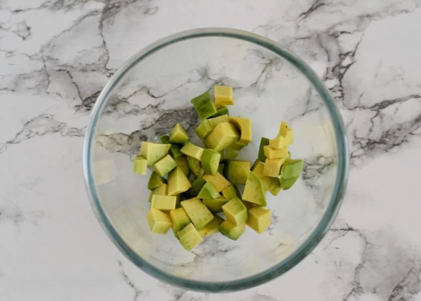 Нарежьте авокадо кубиками, сбрызните лимонным соком.