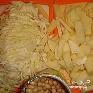 Пока зажарка тушится, подготовьте остальные овощи. Нашинкуйте капусту и порежьте картофель небольшими кубиками (сторона примерно 1 см). Откройте банку с фасолью.