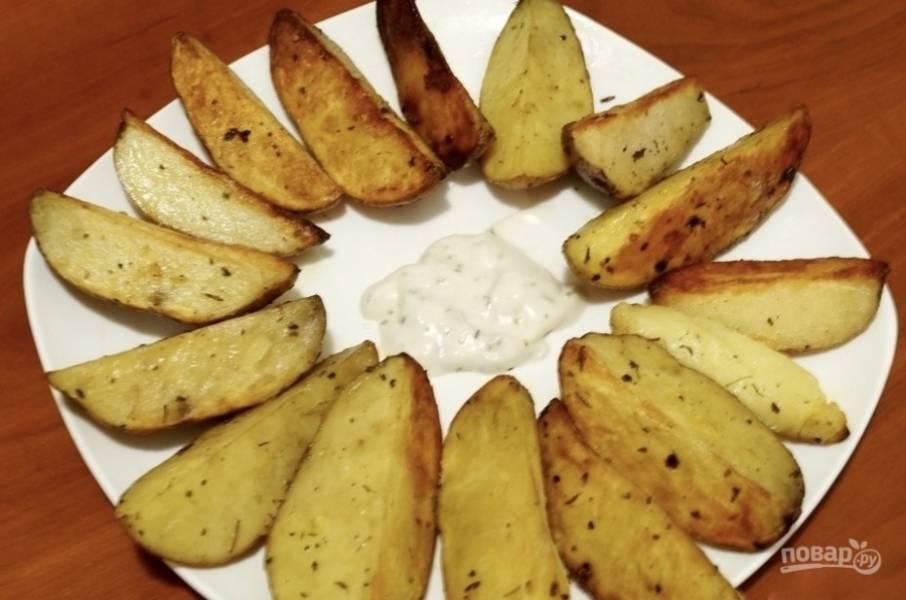 Готово! Подавайте ароматный картофель к столу горячим. Он великолепно сочетается с чесночным соусом. Приятного аппетита!
