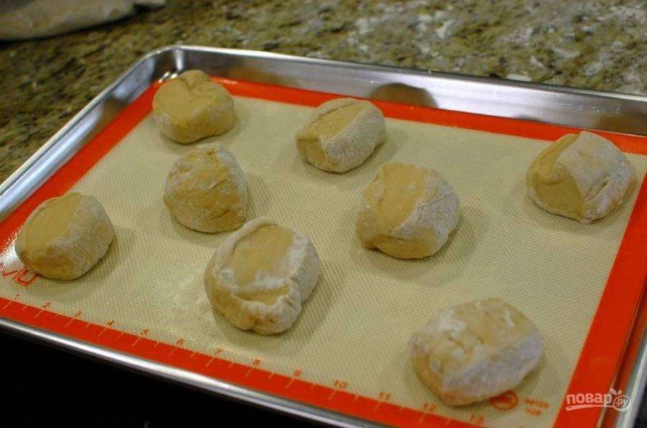 3.Руками сформируйте из каждой части теста грубые булочки, выложите их на противень, застеленный пергаментной бумагой, отложите на 35-40 минут.