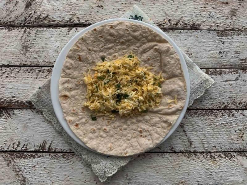 Возьмите лист лаваша, выложите на него подготовленную начинку.